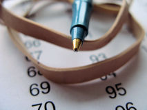 Closeup of pen and paper. This is a macro closeup of the tip of a pen on rubber bands and paper with numbers on it. Still life composition Stock Images