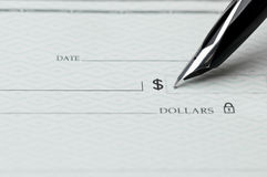 Closeup of pen writing on a blank bank check royalty free stock photography