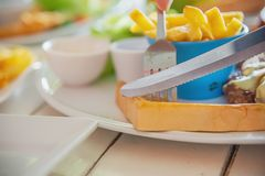Closeup of people eat bread in steak with sausage french fries and salad dish. People with fast food concept royalty free stock photography