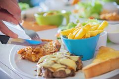 Closeup of people eat steak with sausage french fries and salad dish. People with fast food concept stock images