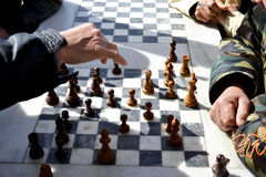 Hands of people playing chess outdoors Stock Photos