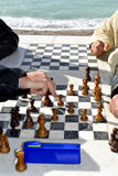 Hands of people playing chess outdoors Stock Images