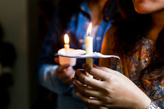 Closeup of people holding candle vigil in dark seeking hope Royalty Free Stock Image