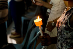 Closeup of people holding candle vigil in dark seeking hope Royalty Free Stock Photography