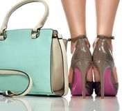 Closeup perfect female legs wearing high heels shoes and woman bag. On white background Stock Images