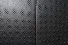 Closeup perforated artificial black leather background texture.  Stock Images