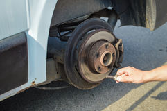 Closeup of person changing vehicle tire with bare hands. Outdoors background Stock Photos