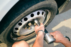Closeup of person checking fixing bolts on vehicle tire with bare hands. Royalty Free Stock Photography