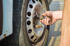 Closeup of person checking fixing bolts on vehicle tire with bare hands. Stock Photo