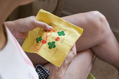 Closeup on person embroidering cross stitch with needle and thre Royalty Free Stock Photos