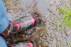Closeup of person jumping in rain puddle with rubber boots on, s Stock Image