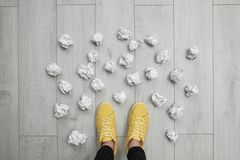 Closeup of person`s feet surrounded by crumpled paper on floor, top view. Lack of ideas royalty free stock image