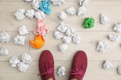 Closeup of person`s feet surrounded by crumpled paper on floor, top view. Lack of ideas stock image