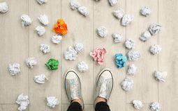 Closeup of person`s feet surrounded by crumpled paper on floor, top view. Lack of ideas royalty free stock photography