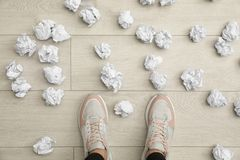 Closeup of person`s feet surrounded by crumpled paper on floor, top view. Lack of ideas stock photography