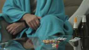 A closeup of a person with signs of a cold illness covered with a blanket, sits in an apartment on the couch and. Measures body temperature with a thermometer stock footage
