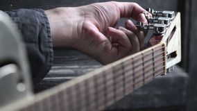 Closeup of hand tuning guitar. Closeup perspective view of Caucasian young man hand tuning and playing on acoustic Dobson metal guitar on dark background stock video footage