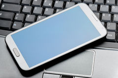Closeup of a phablet on laptop Royalty Free Stock Photos