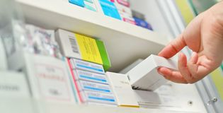 Pharmacist hand holding medicine box in drugstore stock images