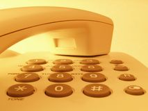 Closeup of a phone. Yellow toned phone Royalty Free Stock Images