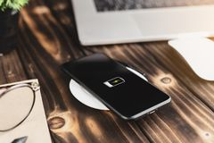 Closeup phone charging on wireless charger device Stock Photos