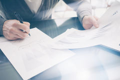 Closeup photo account manager working at the wood table with new business project.Holding pen hand, signs document and. Analyze plans. Horizontal mockup, sunny Royalty Free Stock Photo