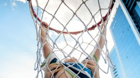 Closeup photo of active 3 years old toddler boy holding on basketball net ring. Concept of active and sporty children. Closeup image of active 3 years old stock photos
