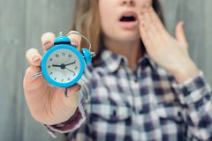 Closeup photo of alarm clock in hand and yawning woman on backgr stock images