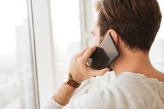 Closeup photo from back of man with short dark hair looking through window, while having mobile call on black cell phone stock image