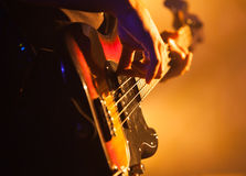 Closeup photo of bass guitar player. Close-up photo of bass guitar player, soft selective focus, live rock music theme Stock Photography