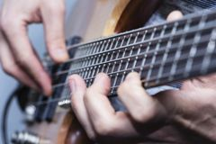 Closeup photo of bass guitar player hands, soft selective focus, live music theme.  stock photo