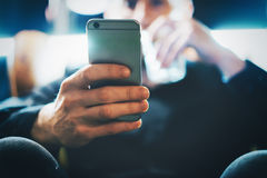 Closeup photo bearded businessman working on modern loft office. Man sitting in vintage chair, drinking glass water. Using contemporary smartphone, blurred Stock Images