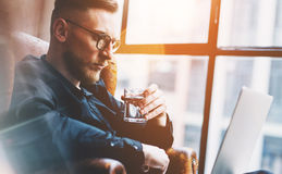 Closeup photo bearded businessman working on modern loft office. Man sitting in vintage chair, holding glass water. Bearded young businessman working on modern Stock Images