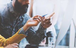 Closeup photo of bearded man and woman working together in modern office. Girl holding a pen in hand pointing to Royalty Free Stock Photo