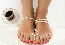 Closeup photo of beautiful female feet with red pedicure  on white and decorated with pearls Stock Photos