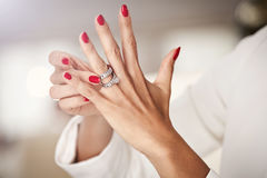 Closeup photo of a beautiful female hands with red nails and ele Stock Photos