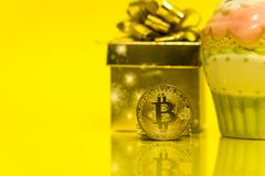 Bitcoin cryptocurrency celebrating birthday - 10 years, coin with golden present behind it, with yellow copy space. Closeup photo of Bitcoin cryptocurrency royalty free stock photography