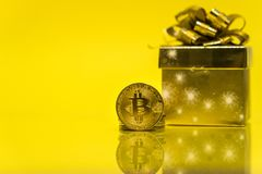 Bitcoin cryptocurrency celebrating birthday - 10 years, coin with golden present behind it, with yellow copy space. Closeup photo of Bitcoin cryptocurrency royalty free stock images