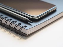 Closeup Photo of Black Smartphone Near Black and Grey Pencil on Black Spiral Notebook Stock Photos