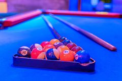 Blue billiard table, balls and cue Royalty Free Stock Photography