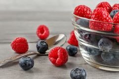 Closeup photo of bowl of blueberries and raspberries mix, some s. Pilled on the gray wood desk and silver spoon next to it Royalty Free Stock Photos