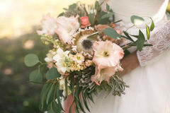 Closeup photo of a bridal bouquet of exotic flowers and greens. Closeup photo of a wedding bouquet of exotic flowers and greens in the hands of the bride Stock Photography