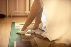 Closeup photo of bride putting on white shoes Royalty Free Stock Photos