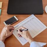 Businessman filling timesheet. Closeup photo of businessman filling weekly time sheet Stock Photo
