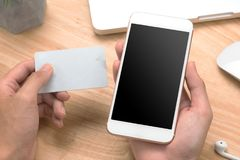 Closeup photo businessman holding hand credit card and using smartphone. Online payments plastic card. Horizontal mockup. Blurred. Film effect stock photo