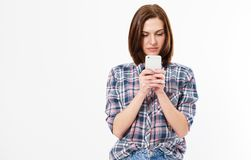 Closeup photo of casually-dressed European girl standing isolated on white background looking attentively at screen of cellphone, stock photography