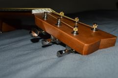 Closeup photo of a child`s acoustic guitar head stock and tuning pegs. Closeup photo of a child`s brown acoustic guitar ready for music lessons Royalty Free Stock Photography