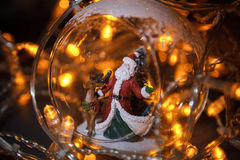 Closeup photo of christmas glass toy with Santa Claus and dear i. Nside. Yellow garland background Royalty Free Stock Images