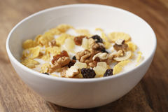 Closeup photo of corn flakes with fruits and nuts in white bowl on wood table Royalty Free Stock Photos