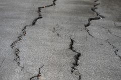 Closeup photo of cracked asphalt. In local road or street after earthquake or el nino. Textured pattern background. Natural disaster Stock Photo